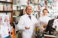 Φαρμακοποιοί που στέκονται με ένα γραφείο μετρητών στοκ εικόνες με δικαίωμα ελεύθερης χρήσης
