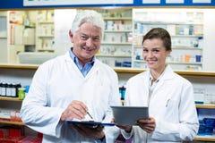 Φαρμακοποιοί που συζητούν στην ψηφιακές ταμπλέτα και την περιοχή αποκομμάτων στο φαρμακείο στοκ εικόνα