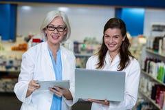 Φαρμακοποιοί που χρησιμοποιούν την ψηφιακά ταμπλέτα και το lap-top στο φαρμακείο στοκ φωτογραφίες