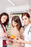 Φαρμακοποιός, γιατρός και πελάτης μέσα στο φαρμακείο Στοκ Φωτογραφία