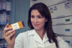 Φαρμακοποιός γυναικών που φαίνεται ιατρική στο φαρμακείο στοκ εικόνες