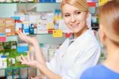 Φαρμακοποιός και ένας πελάτης που επιλέγει την ιατρική στοκ εικόνες