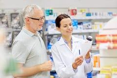 Φαρμακοποιός και ανώτερο φάρμακο αγοράς ατόμων στο φαρμακείο στοκ εικόνα