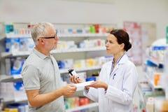 Φαρμακοποιός και ανώτερο φάρμακο αγοράς ατόμων στο φαρμακείο στοκ εικόνα με δικαίωμα ελεύθερης χρήσης