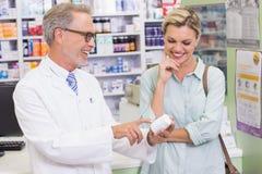 Φαρμακοποιός και πελάτης που εξετάζουν την ιατρική στοκ φωτογραφία