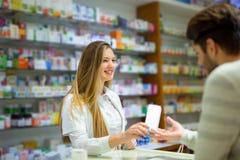 Φαρμακοποιός και πελάτης σε ένα φαρμακείο Στοκ Φωτογραφίες