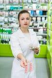 Φαρμακοποιός με μερικά χάπια στις σημειώσεις φουσκαλών και δολαρίων στοκ φωτογραφίες