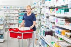 Φαρμακοποιός με τα προϊόντα στα καλάθια στο φαρμακείο στοκ φωτογραφίες με δικαίωμα ελεύθερης χρήσης