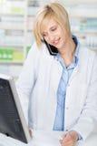 Φαρμακοποιός με τη συνταγή που χρησιμοποιεί το ασύρματο τηλέφωνο κοιτάζοντας Στοκ εικόνες με δικαίωμα ελεύθερης χρήσης
