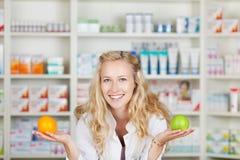 Φαρμακοποιός με τη Apple και το πορτοκάλι Στοκ εικόνες με δικαίωμα ελεύθερης χρήσης