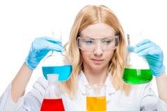 Φαρμακοποιός με τους πολύχρωμους σωλήνες δοκιμής σε ένα λευκό στοκ φωτογραφία με δικαίωμα ελεύθερης χρήσης