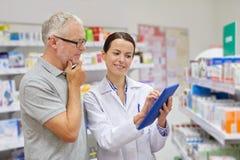 Φαρμακοποιός με το PC ταμπλετών και ανώτερο άτομο στοκ εικόνα με δικαίωμα ελεύθερης χρήσης