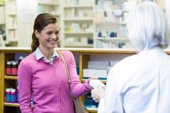 Φαρμακοποιός που δίνει το κιβώτιο ιατρικής στον πελάτη στοκ εικόνες