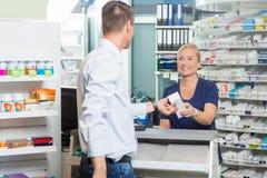 Φαρμακοποιός που δίνει το προϊόν στον πελάτη στο φαρμακείο στοκ φωτογραφίες
