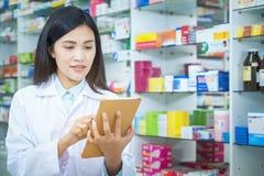 Φαρμακοποιός που απασχολείται με έναν υπολογιστή ταμπλετών στην εκμετάλλευση φαρμακείων σε το στο χέρι της διαβάζοντας τις πληροφ στοκ φωτογραφίες με δικαίωμα ελεύθερης χρήσης