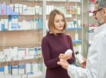 Φαρμακοποιός που βοηθά τη γυναίκα με την επιλογή στο φαρμακείο στοκ φωτογραφίες