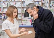 Φαρμακοποιός που βοηθά το άτομο με τον πόνο δοντιών στο φαρμακείο στοκ φωτογραφία