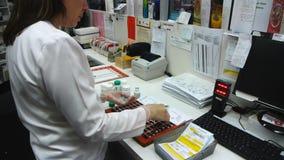 Φαρμακοποιός που γεμίζει το πολυ πακέτο δόσεων με τα φάρμακα απόθεμα βίντεο