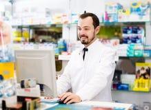 Φαρμακοποιός που γράφει κάτω την κατάταξη των φαρμάκων στοκ εικόνα
