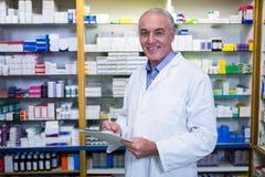 Φαρμακοποιός που γράφει στην περιοχή αποκομμάτων στο φαρμακείο στοκ φωτογραφία με δικαίωμα ελεύθερης χρήσης