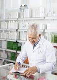 Φαρμακοποιός που γράφει στην περιοχή αποκομμάτων στο φαρμακείο στοκ εικόνα