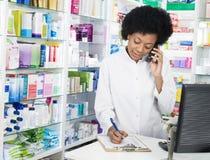 Φαρμακοποιός που γράφει στην περιοχή αποκομμάτων χρησιμοποιώντας το ασύρματο τηλέφωνο Στοκ εικόνα με δικαίωμα ελεύθερης χρήσης