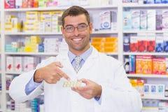 Φαρμακοποιός που δείχνει τα πακέτα φουσκαλών στοκ φωτογραφία