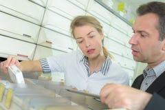 Φαρμακοποιός που εξετάζει τη συνταγή και την ιατρική στο φαρμακείο στοκ φωτογραφία με δικαίωμα ελεύθερης χρήσης