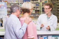 Φαρμακοποιός που εξηγεί κάτι σε έναν πελάτη στοκ φωτογραφία με δικαίωμα ελεύθερης χρήσης