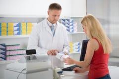 Φαρμακοποιός που εξηγεί τα φάρμακα στον πελάτη στοκ εικόνα με δικαίωμα ελεύθερης χρήσης