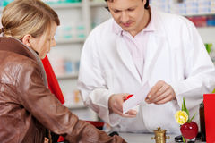 Φαρμακοποιός που εξηγεί την ιατρική συνταγών στον πελάτη Στοκ Εικόνες
