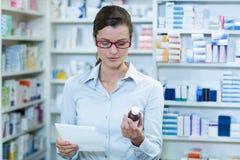 Φαρμακοποιός που ελέγχει στο εμπορευματοκιβώτιο συνταγών και ιατρικής στοκ φωτογραφία με δικαίωμα ελεύθερης χρήσης