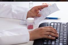 Φαρμακοποιός που ελέγχει τις πληροφορίες για τα φάρμακα Στοκ Φωτογραφίες