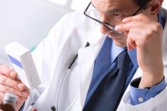 Φαρμακοποιός που κάθεται αρσενικός στις σημειώσεις ανάγνωσης γραφείων Στοκ Φωτογραφίες
