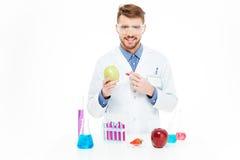 Φαρμακοποιός που κάνει την έγχυση των ΓΤΟ στο μήλο Στοκ εικόνα με δικαίωμα ελεύθερης χρήσης