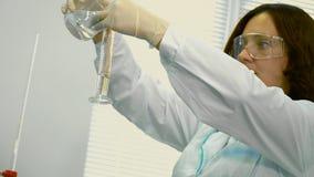 Φαρμακοποιός που μετρά το νερό στη φιάλη μέτρου απόθεμα βίντεο