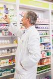 Φαρμακοποιός που παίρνει την ιατρική από το ράφι Στοκ Φωτογραφίες