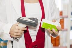 Φαρμακοποιός που παίρνει το διαβασμένο γραμμωτό κώδικα της συνταγής γιατρών Στοκ Εικόνα