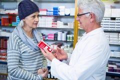 Φαρμακοποιός που παρουσιάζει ιατρική στον πελάτη στοκ εικόνες