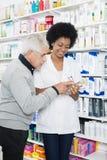 Φαρμακοποιός που παρουσιάζει πληροφορίες για το προϊόν στον ανώτερο πελάτη Στοκ εικόνες με δικαίωμα ελεύθερης χρήσης