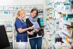 Φαρμακοποιός που παρουσιάζει πτώσεις ματιών στον πελάτη ενώ στοκ φωτογραφία με δικαίωμα ελεύθερης χρήσης