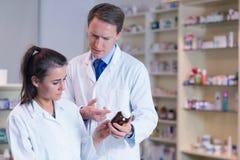 Φαρμακοποιός που παρουσιάζει φάρμακο στον εκπαιδευόμενό του στοκ φωτογραφία με δικαίωμα ελεύθερης χρήσης