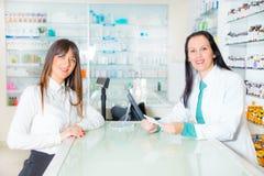 Φαρμακοποιός που προτείνει το ιατρικό φάρμακο στον αγοραστή στο φαρμακείο στοκ φωτογραφία