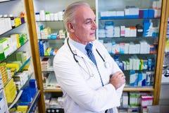 Φαρμακοποιός που στέκεται με τα όπλα που διασχίζονται στοκ εικόνες