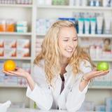 Φαρμακοποιός που συγκρίνει τη Apple και το πορτοκάλι Στοκ εικόνα με δικαίωμα ελεύθερης χρήσης