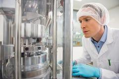 Φαρμακοποιός που χρησιμοποιεί τα μηχανήματα για να κάνει την ιατρική στοκ εικόνες