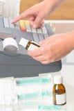 Φαρμακοποιός που χρησιμοποιεί τον κατάλογο μετρητών Στοκ Εικόνα