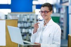 Φαρμακοποιός που χρησιμοποιεί το lap-top στο φαρμακείο στοκ εικόνα