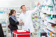 Φαρμακοποιός σε Labcoat που αφαιρεί την ιατρική για το θηλυκό στοκ φωτογραφία