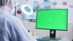 Φαρμακοποιός στην άσπρη φόρμα που λειτουργεί στον πράσινο υπολογιστή οθόνης απόθεμα βίντεο